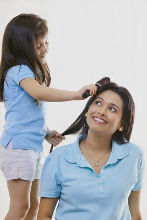 Girl brushing mothers hair
