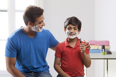 Father and son shaving Фото со стока