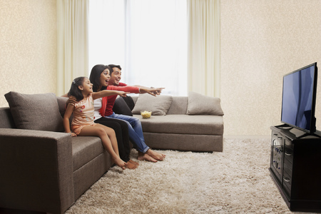 Mother, father and daughter sitting on sofa and pointing at television