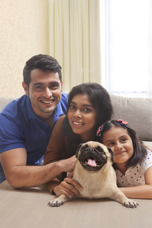 Portrait of smiling family with daughter and pug