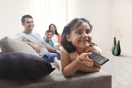 Smiling young girl watching TV with family Stock Photo