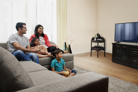 Young boy eating popcorn and watching TV with family Stock Photo