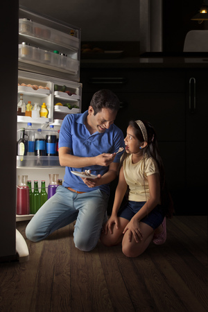 refrigerator: Father and daughter kneeling down in front of open refrigerator and eating cake Stock Photo
