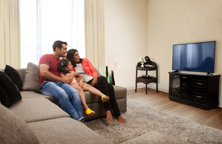 Mother, father and daughter sitting on sofa and watching TV