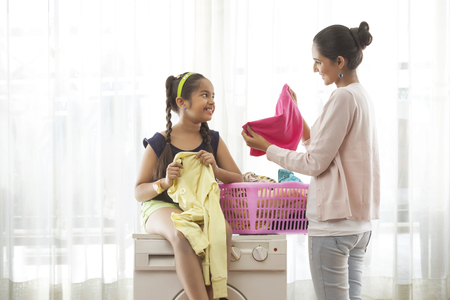 preadolescent: Daughter sitting on washing machine mother folding laundry Stock Photo