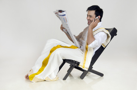 dhoti: South Indian man talking on mobile phone while reading newspaper Stock Photo