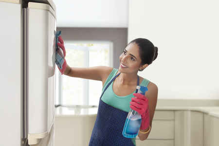 refrigerator: Young woman cleaning refrigerator with spray cleaner Stock Photo