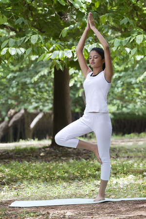 Young woman practicing yoga in a park