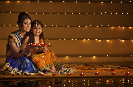 Portrait of mother and daughter with tray of diyas