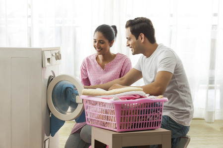 Young couple loading washing machine together