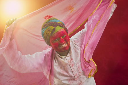 Young Indian man With Colored Face Dancing During Holi Color festival Stock Photo