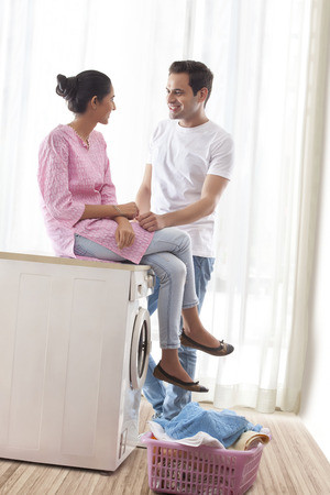 Young couple talking in laundry room