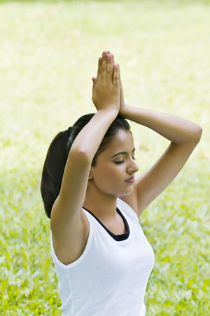 Young woman doing yoga with hands in prayer position Stock Photo