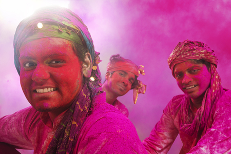kurta: Young Indian Men sitting on floor, covered in colored powder during holi color festival