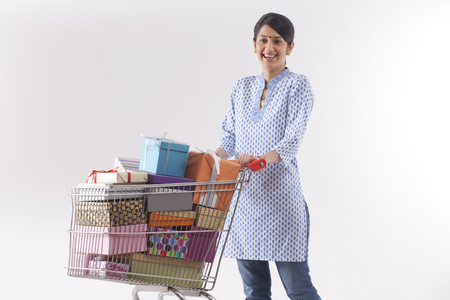 Young woman holding a cart full of gifts Stock Photo