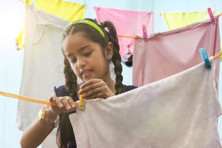 Young girl drying a cloths on a clothesline Stock Photo