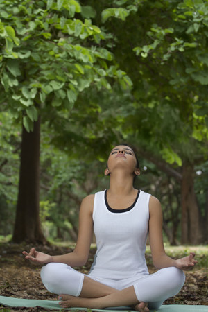 cross legged: Young woman in lotus position meditating in a park