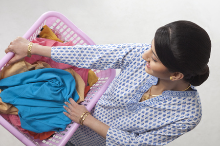 Young woman holding a basket of clothes Stock fotó