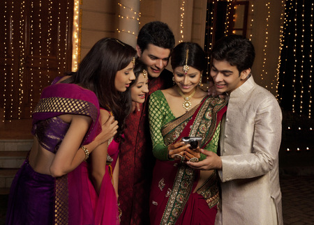 kurta: Friends looking at a picture on a camera