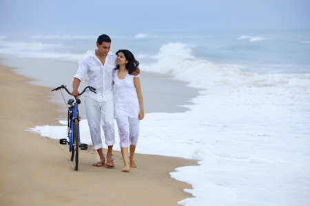 front view: Couple walking on a beach with a bicycle