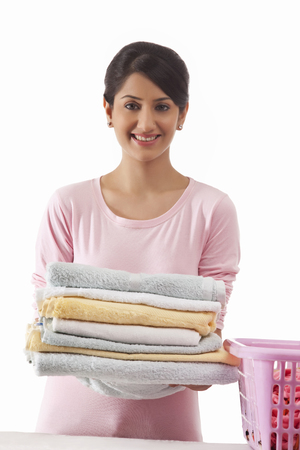 front house: Young woman holding a pile of towels