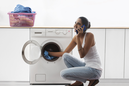 stereotypical housewife: Young woman loading washing machine and talking on mobile phone