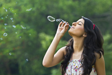 Young woman blowing bubbles in a park