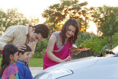 kurta: Woman putting tika on new car
