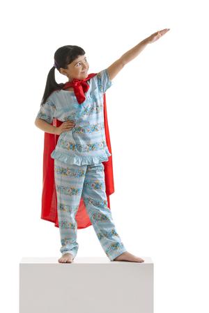 pretending: Girl pretending to be superman Stock Photo