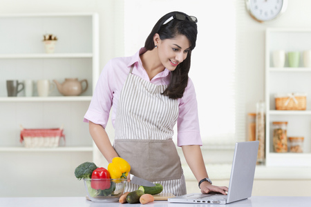 kitchen island: Businesswoman using laptop while preparing food in kitchen at home Stock Photo