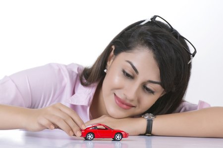Smiling businesswoman looking at toy car against white background