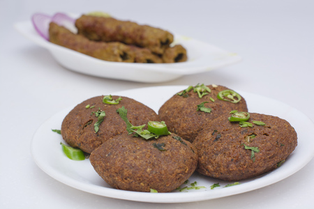 Close-up of cutlets with seekh kababs in background on table