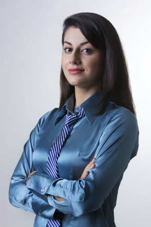 welldressed: Portrait of confident Indian businesswoman standing arms crossed against gray background