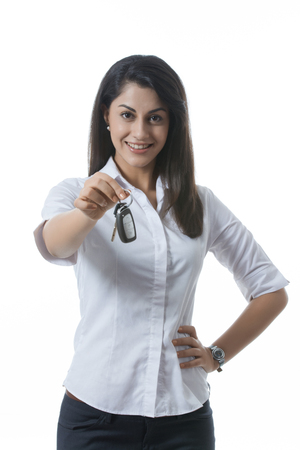 welldressed: Portrait of confident Indian businesswoman holding car keys against white background Stock Photo