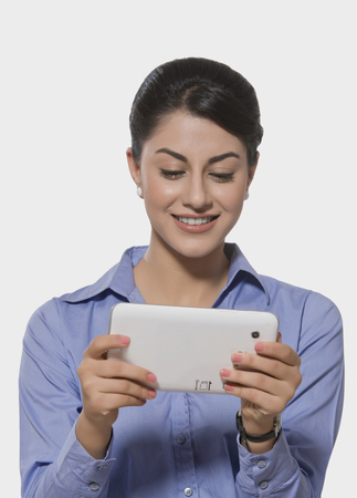 welldressed: Smiling Indian businesswoman using tablet PC over white background