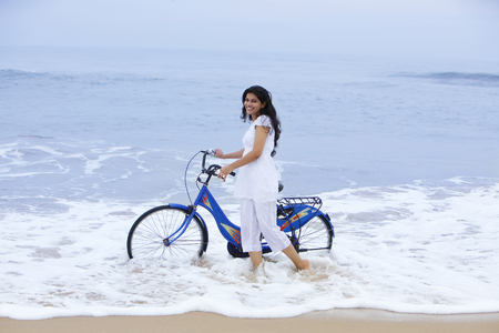 toothy: Portrait of a woman with a bicycle at a beach