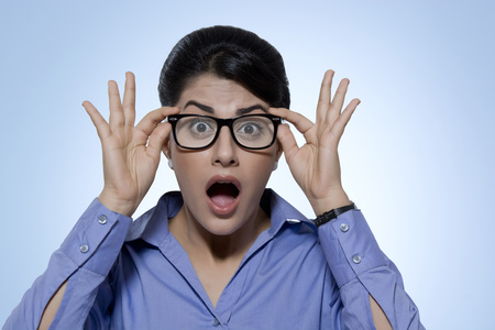 welldressed: Portrait of shocked businesswoman wearing glasses against blue background