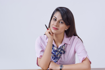 Portrait of confident Indian businesswoman leaning on office desk