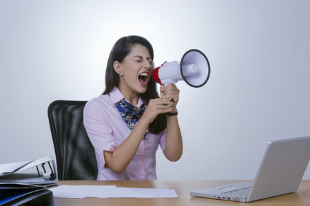 welldressed: Frustrated businesswoman yelling in megaphone at office desk Stock Photo