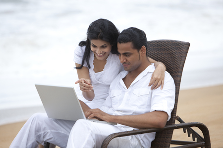 toothy: Couple with a laptop at a beach Stock Photo