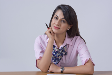 welldressed: Thoughtful businesswoman leaning on office desk