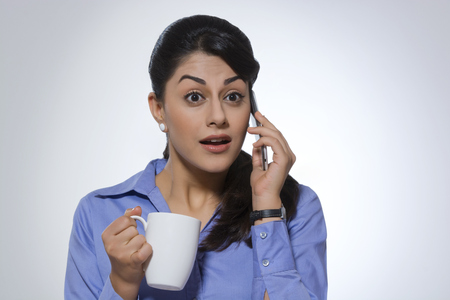 welldressed: Surprised businesswoman with coffee mug using phone against gray background