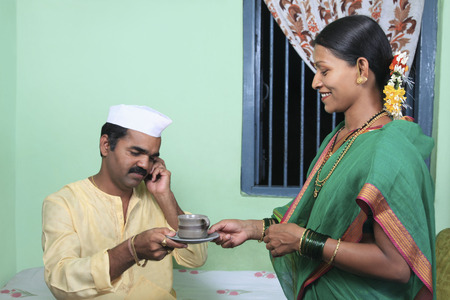 toothy: Woman giving her husband a cup of tea Stock Photo