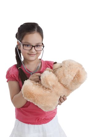 Portrait of little girl playing doctor with teddy bear