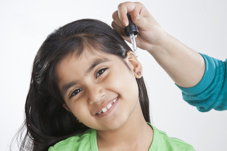 Portrait of little girl getting drops put in ear