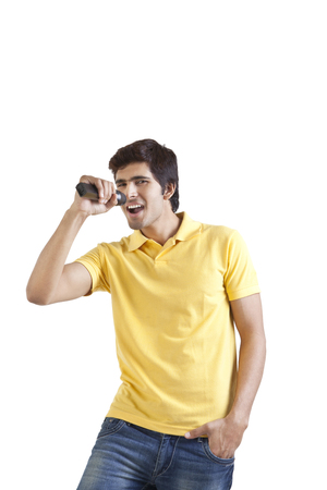 Portrait of young man with a microphone singing Stock Photo