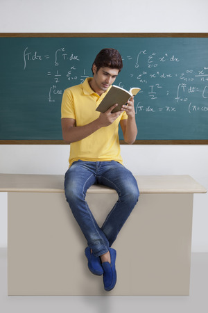 formula one: College student sitting on a table reading a book