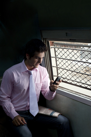 25 30: Businessman reading an sms in a train