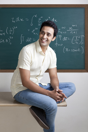 College student sitting on a table smiling Stock Photo