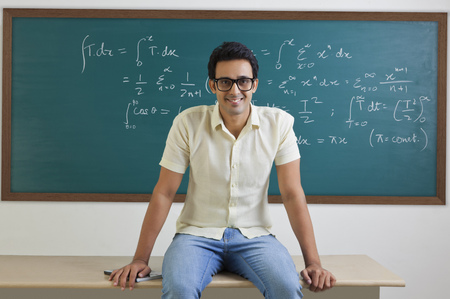 Portrait of college student sitting on a table smiling